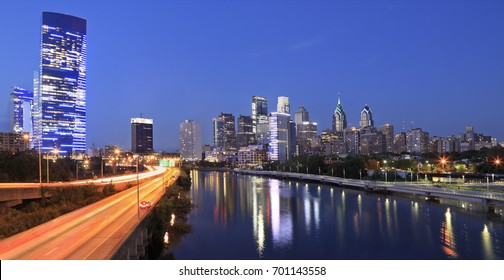 The skyline of Philadelphia of dusk. Schuylkill expressway traffic runs parallel to Schuylkill River.