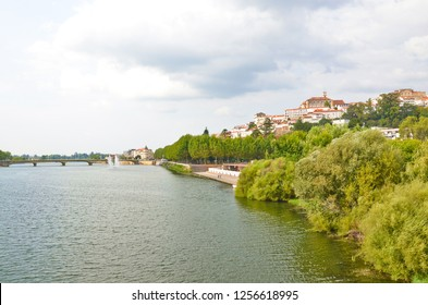 Skyline of portuguese Coimbra along the Mondego River. The dominant of this beautiful historical city is a bell tower belonging to the famous University of Coimbra. Photo: Sep 4th 2018