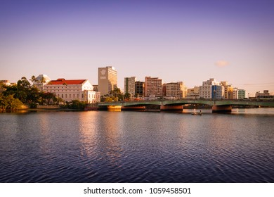the skyline of Recife in Pernambuco, Brazil with its historic buildings and bridges by the Capibaribe river at sunset.