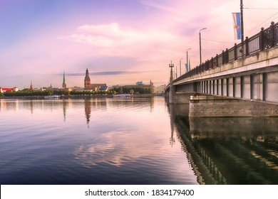Skyline of Riga and the river Daugava in the morning, Latvia. Riga castle, St. Saviour's Anglican Church, Church of St. Jacob, Dome cathedral, Stone bridge from left to right . Delicate pink morning