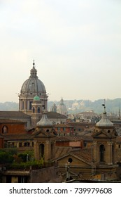 The skyline of Rome early in the morning with the mist from Trinità dei Monti  - In the foreground San Carlo al Corso dome by Pietro da Cortona and tower bell of Sant'Atanasio