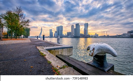 Skyline of Rotterdam at sunrise during the fall with a river on the foreground