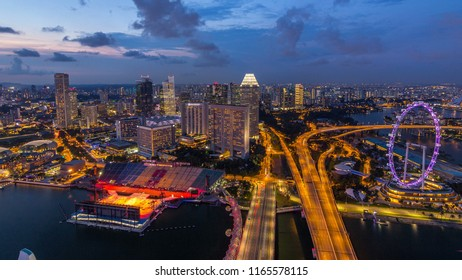 Skyline of Singapore with famous Singapore Ferries Wheel day to night transition timelapse at twilight. Aerial view from rooftop with illuminated skyscrapers
