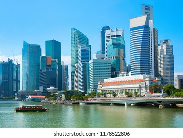 Skyline of Singapore with financial district view and tour boat by embankment