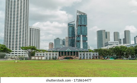 Skyline with Singapore Recreation Club and skycrapers on background view . Green lawn and clouds on a the sky