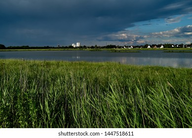 skyline of the small city Brake (Unterweser), district Wesermarsch (Germany) far away behind the biotope called Kleipütte in sunlight under a dark rain cloud