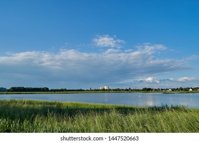 skyline of the small city Brake (Unterweser), district Wesermarsch (Germany) far away behind the biotope called Kleipütte under scenic vivid blue sky with clouds