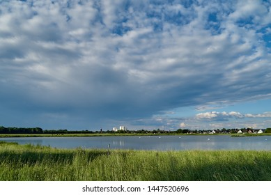 skyline of the small city Brake (Unterweser), district Wesermarsch (Germany) far away behind the biotope called Kleipütte under a scenic vivid cloudy sky