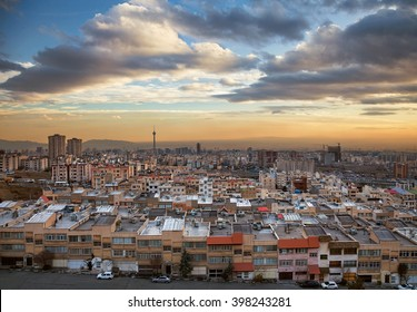 Skyline of Tehran with Milad Tower, residential and commercial buildings at a dramatic sunset with beautiful cloudy sky.