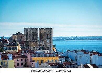 Skyline with the towers of the cathedral and colourful houses of the Alfama district in Lisbon on a cloudy Winter afternoon.