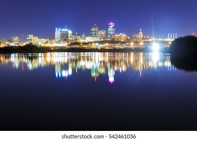 A skyline view of Kansas City over the Missouri River with reflections on the water.