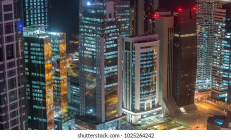 The skyline of the West Bay area from top in Doha timelapse, Qatar. Illuminated modern skyscrapers aerial view from rooftop at night. Traffic on the road