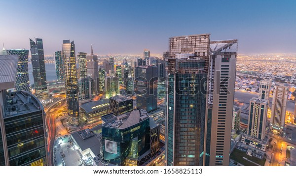 Skyline of the West Bay area from top in Doha night to day transition timelapse, Qatar. Illuminated modern skyscrapers aerial view from rooftop at morning before sunrise