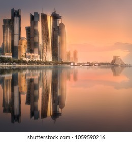 The skyline of West Bay and Doha City Center during sunset with reflection of buildings on water, Qatar