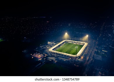 A skyline/horizon view with a football stadium seen from above on a foggy night with the stadium lights on and sporters playing soccer.