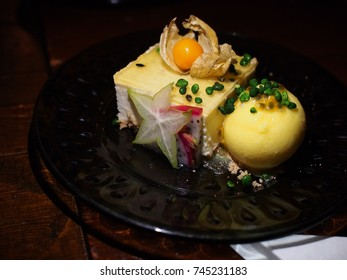 Skyr mousse cake with passion fruit ice cream garnished with star fruit, goodberry  on black plate