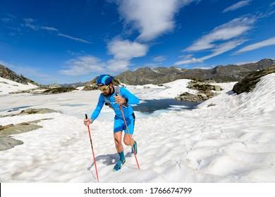 Skyrunner man in action going uphill on snow