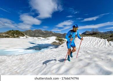 Skyrunner man uphill in a snowy stretch