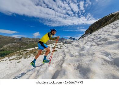 Skyrunner runner uphill in a snowy stretch
