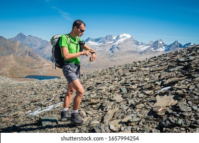 skyrunner training over the mountains watching heart rate monitor. italian Alps. Gran Paradiso National Park, Italy