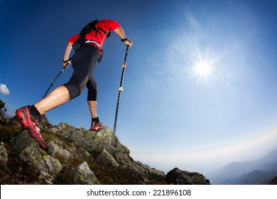 Skyrunning: rear view of a young male runner walking along a mountain trail. Sunny summer day. West Alps, Italy, Europe.