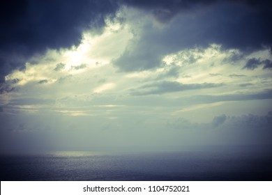 Skyscape or cloudscape. Overcast evening sky with stormy dark clouds moving over sea surface. Weather