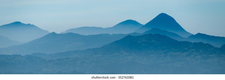Skyscape of cold blue mountains with mist and fog close to Quetzaltenango in Guatemala