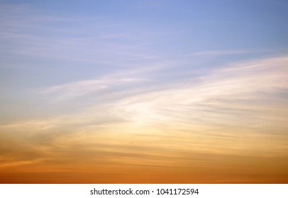Skyscape of simple gradient colors of orange and white clouds against blue sky