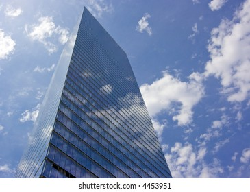 Skyscraper with clouds reflecting off of the windows