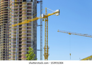 skyscraper Construction site with yellow cranes on blue bright sky
