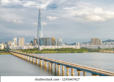 Skyscraper at downtown of Seoul in South Korea on cloudy sky background. Scenic modern tower and Jamsil Railway Bridge over the Han River (Hangang). Wonderful cityscape.