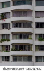 Skyscraper facade with curve balcony and decorated with small bushes.