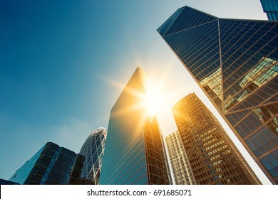 Skyscraper glass facades on a bright sunny day with sunbeams in the blue sky. Modern buildings in Paris business district La Defense. Economy, finances, business activity concept. Bottom up view - Shutterstock ID 691685071
