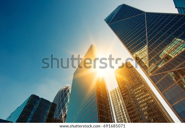 Skyscraper glass facades on a bright sunny day with sunbeams in the blue sky. Modern buildings in Paris business district La Defense. Economy, finances, business activity concept. Bottom up view