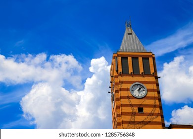 Skyscraper with an orange brick  clock tower against the blue sky with beautiful clouds. Architecture  of Dnipro city, Dnepropetrovsk,  Ukraine