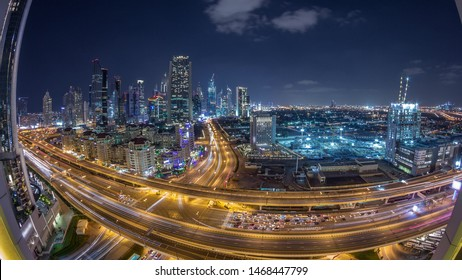 Skyscrapers aerial paniramic view in downtown and financial district Dubai night timelapse, traffic on highways. United Arab Emirates with illuminated towers and cloudy sky