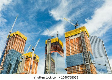 Skyscrapers construction site for modern buildings in New York. Cranes and scaffolding used to build tall structures, blue sky on background.