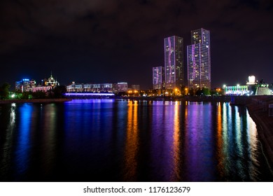 Skyscrapers and different commercial buildings in the downtown on Ishim River side with bridge. Colorful night in Astana, capital of Kazakhstan. Reflection on the water.