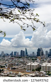 The skyscrapers in downtown Bangkok, the capital of Thailand in southeast Asia, with white cloud and blue sky on a sunny day in vertical view with foreground of a blurred tree.