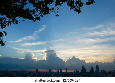The skyscrapers in downtown Bangkok cityscapes, the capital of Thailand in southeast Asia, with rain cloud and sunset in horizontal view from terrace of a condominium which has a tree on foreground.