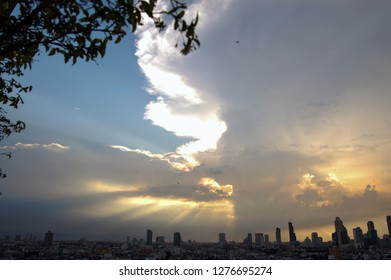 The skyscrapers in downtown Bangkok cityscapes, the capital of Thailand in southeast Asia, with golden sun rays through white cloud at sunset in summer in horizontal view.
