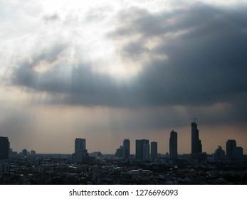 The skyscrapers in downtown Bangkok cityscapes, the capital of Thailand in southeast Asia, with beam of light from the sun through the grey cloud  in summer in horizontal view.