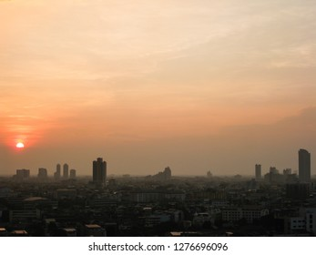 The skyscrapers in downtown Bangkok cityscapes, the capital of Thailand in southeast Asia, with fog and golden sunshine evening at sunset in winter in horizontal view.