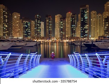 Skyscrapers of Dubai Marina against black sky, behind a pier bridge illuminated with blue light. Dubai Marina is an artificial canal city, carved along a two mile stretch of Persian Gulf shoreline.