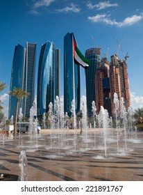 Skyscrapers of modern Abu Dhabi, capital of United Arab Emirates. Fountains and UAE flag at foreground.