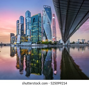 Skyscrapers in Moscow-City with reflection in the Moscow River in the sunset pink sky