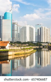 Skyscrapers, office buildings and luxury hotels towers reflects in the water of a canal in Jakarta on a sunny day in Indonesia capital city
