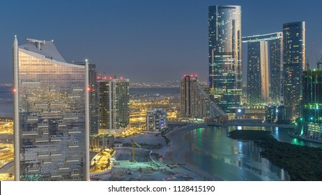 Skyscrapers on Al Reem Island in Abu Dhabi day to night transition timelapse after sunset from above. Aerial citiscape from Al Reem Island with illuminated buildings
