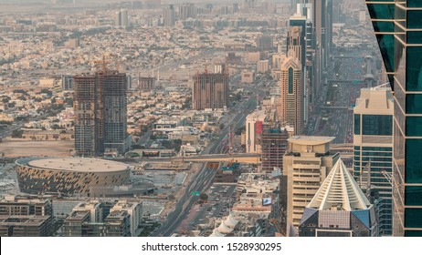 Skyscrapers on Sheikh Zayed Road and DIFC aerial timelapse in Dubai, UAE. Traffic on a highway near Financial Centre at evening before sunset from business bay rooftop