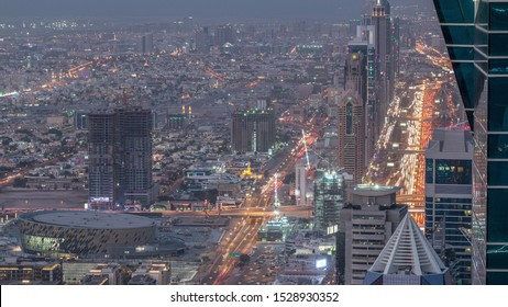 Skyscrapers on Sheikh Zayed Road and DIFC aerial day to night transition timelapse in Dubai, UAE. Traffic on a highway near Financial Centre at evening after sunset from business bay rooftop